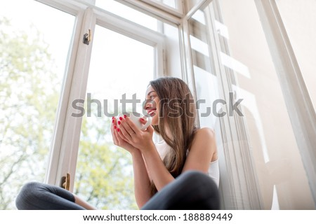 Young and cute lady sitting on the windowsill and looking out the window with cup of coffee in the morning #188889449