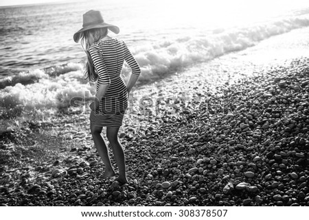 Young and elegant woman in stripped dress with a hat walking to the sea on the beach on sunset. Black and white photo