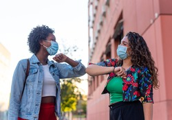 Young and friendly african girl and caucasian girl keeping social distance, greeting each other by bumping elbows instead of hugs, kisses or handshaking, wearing mask for prevent coronavirus infection