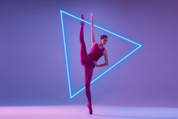 Young and graceful ballet dancer isolated on purple studio background in neon light with glowing triangle. Art, motion, action, flexibility, inspiration concept. Flexible caucasian ballet dancer.