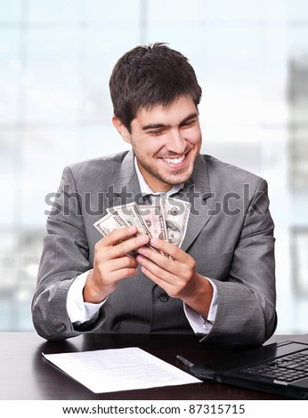Young and handsome business man holding money with happy face