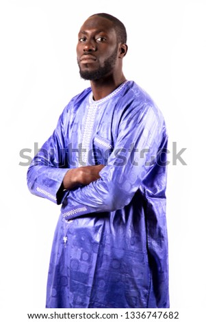 Young and handsome. Handsome young African senegalese man in smart casual jacket holding hands in pockets and traditional smiling while standing against white background #1336747682