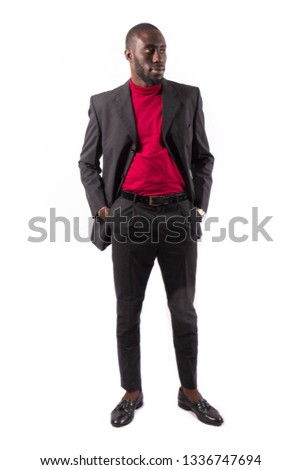 Young and handsome. Handsome young African senegalese man in smart casual jacket holding hands in pockets and traditional smiling while standing against white background #1336747694
