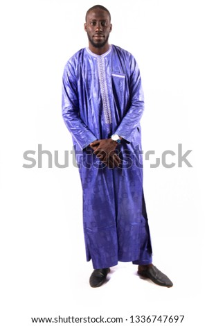Young and handsome. Handsome young African senegalese man in smart casual jacket holding hands in pockets and traditional smiling while standing against white background #1336747697