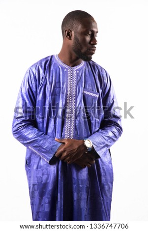 Young and handsome. Handsome young African senegalese man in smart casual jacket holding hands in pockets and traditional smiling while standing against white background #1336747706