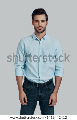 Young and handsome. Handsome young man looking at camera and smiling while standing against grey background #1416442412