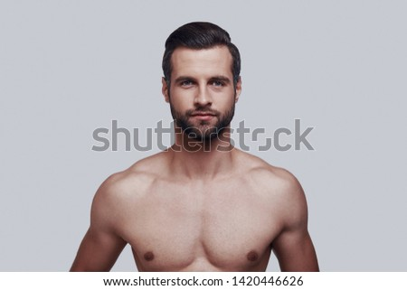Young and handsome. Handsome young man looking at camera and smiling while standing against grey background #1420446626