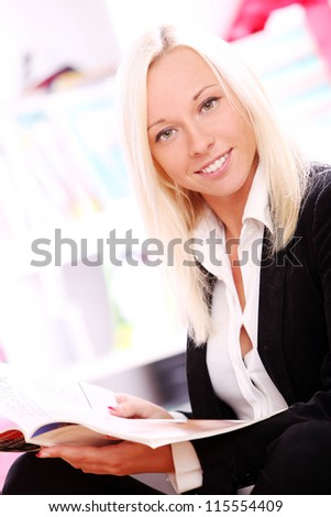 Young and happy blonde relaxing with magazine at home