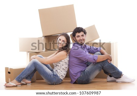 Young and happy couple are carrying boxes to new house