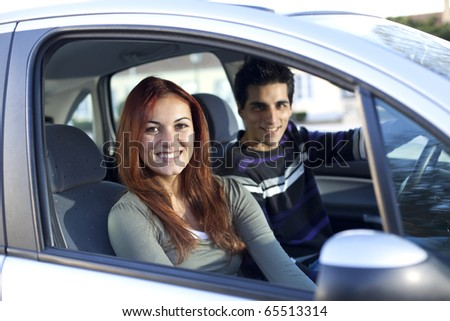 Young and happy couple inside a land vehicle for the begin of a long travel (selective focus with shallow DOF)