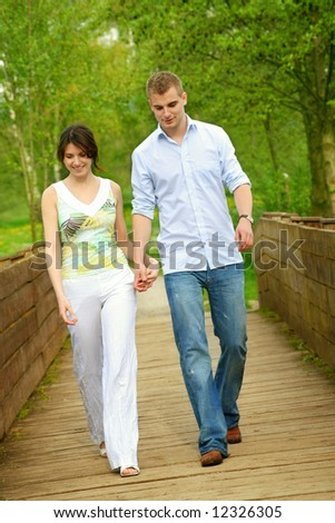young and happy couple taking a walk on a bridge
