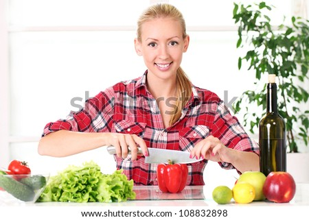 Young and happy girl preparing healthy food in the kitchen