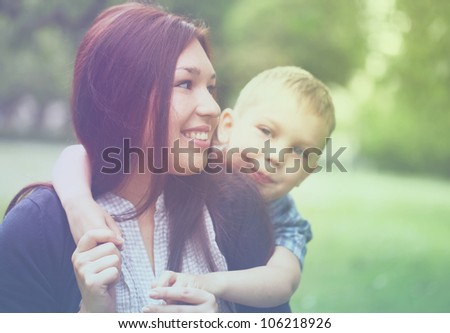 Young and happy mother with her son in the park