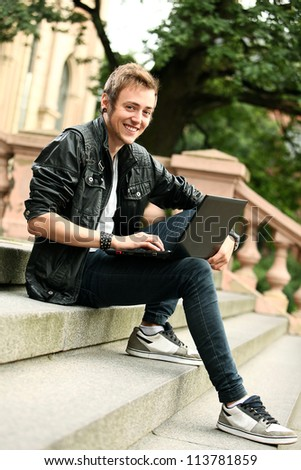 Young and happy student with laptop sitting on a stairs