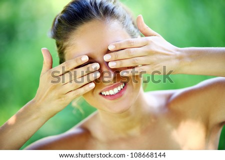 Young and happy woman covering her face with  hands
