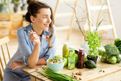 Young and happy woman eating healthy salad sitting on the table with green fresh ingredients indoors