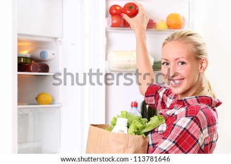 Young and happy woman is putting a food into the fridge