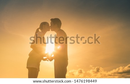 Young and in love. Young couple kissing at sunset.