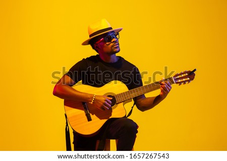 Young and joyful african-american musician playing guitar and singing on gradient orange-yellow studio background in neon light. Concept of music, hobby, festival. Colorful portrait of modern artist. Photo stock ©