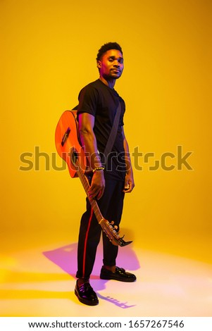 Young and joyful african-american musician playing guitar and singing on gradient orange-yellow studio background in neon light. Concept of music, hobby, festival. Colorful portrait of modern artist. ストックフォト ©