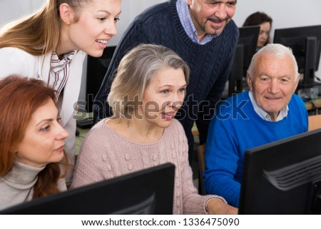 Young and mature  partners grouped around computer monitor  in modern office