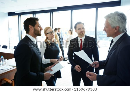 Young and mature politicians in formalwear discussing points of their reports and consulting about ideas