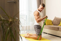 Young and muscular man during home workout with a resistance rubber bands