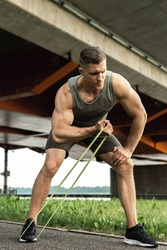 Young and muscular man during workout with a resistance rubber bands on a street. Biceps curls exercise.