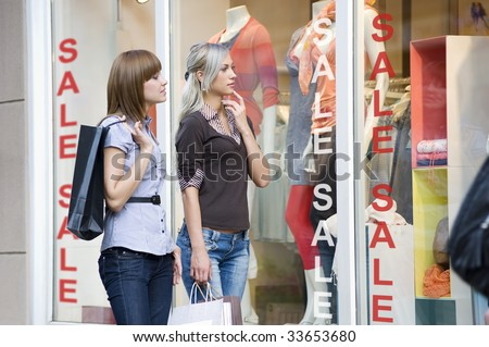 young and nice women in front of a window shop in act to decide what to buy
