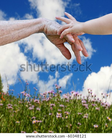 Young and old. Child's hand touching the elderly hand, connection of generations concept