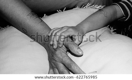 Young and old hands. Hands of child helping an elderly person. Photo taken in black and white.  #622765985