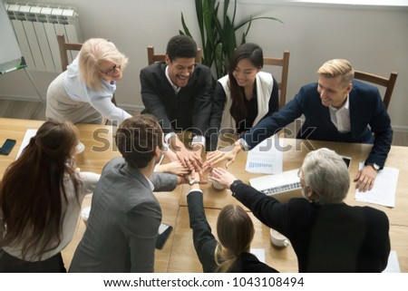 Young and old multiracial business people join pile of stacked hands together at group meeting conference table promising help support, concept of successful teamwork, team building unity, top view