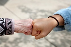 Young and old woman are fist bumping, young and old ethnic contest