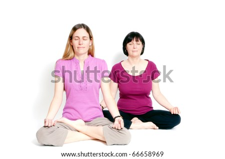 Young and old woman sitting in lotus seat practicing yoga together