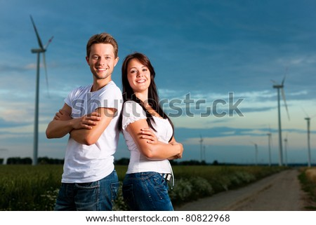 Young and powerful couple in front of energy windmill in the evening; a storm is coming