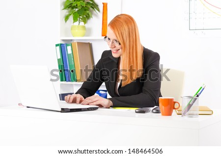 Young and pretty businesswoman in her office working on her laptop and smiling