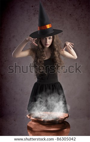 young and pretty girl dressed up for halloween with a huge black witch hat making spells behind a witch's cauldron - stock photo