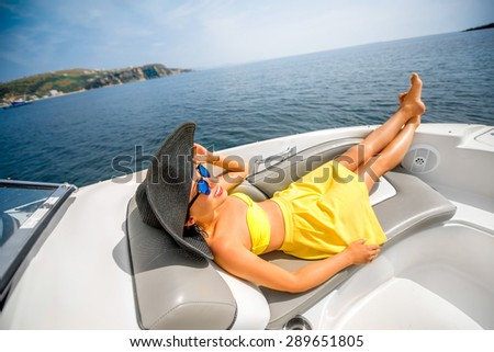 Young and pretty woman in yellow swimsuit with big hat relaxing on the yacht floating in the sea. Luxury summer recreation #289651805