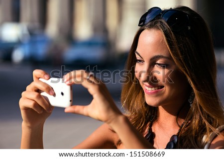 Young and pretty Woman taking photo with her smartphone while sightseeing