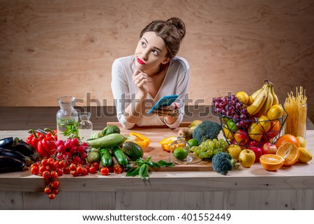 Young and pretty woman using smart phone sitting at the table full of fruits and vegetables in the wooden interior. Counting calories with mobile app. Food and health care concept
