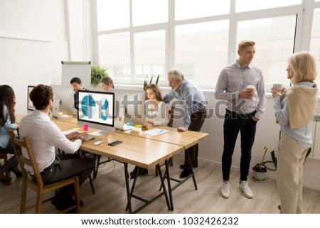 Young and senior employees doing different office activities in coworking space, business people working on shared desk using computers, mentors teaching interns, colleagues talking, teamwork concept
