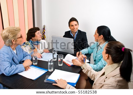 Young and senior people having a business meeting in an office and sitting around table making conversation  and laughing