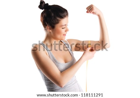 Young and sexy blond woman smile, measuring her arm muscle by measure tape, isolated over white background