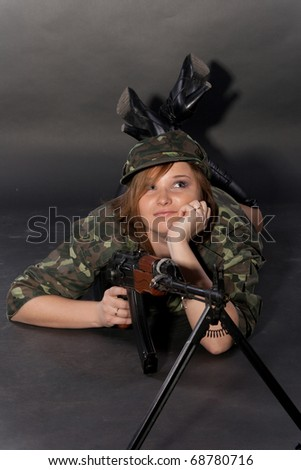 Young and sexy female model in military outfit posing in studio with airsoft AK-series machine gun