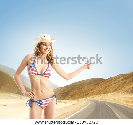 Young and sexy girl in American swimsuit makes the hitch-hiking - stock photo