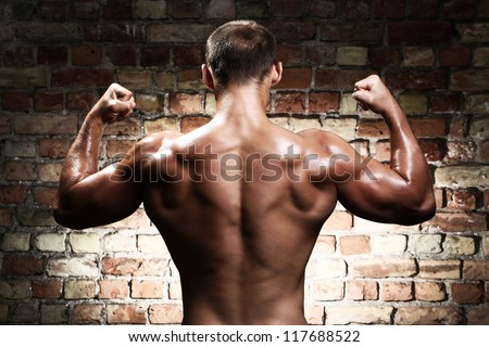 Young and sexy guy with muscular body against a brick wall