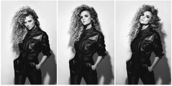 Young and sexy woman with a stylish Afro hairstyle wearing leather biker suit