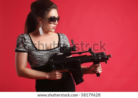 Young and sexy woman with an assault gun.