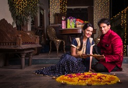 Young and smart Indian Couple in Traditional wear arranging Diya around flower Rangoli on Diwali Festival Night