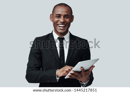 Young and smart. Young African man in formalwear looking at camera and smiling while standing against grey background